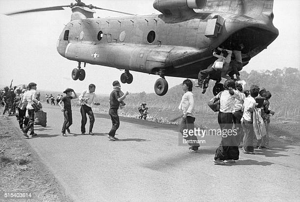 Refugees hang on for dear life as they attempt to board a giant Chinook helicopter as it was taking off here following a supply drop to troops...