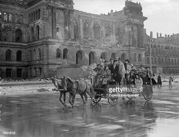 Refugees in Berlin make their way through the bombdamaged city by horse and cart