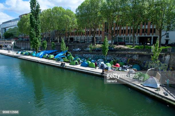 refugees in paris, france - migrants in paris stock photos and pictures