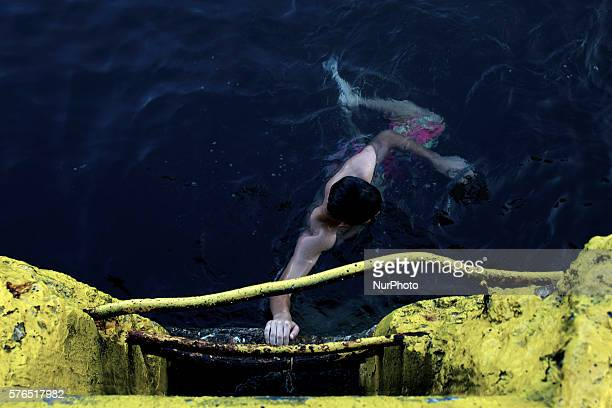 Refugees in Piraeus Port Greece on 15 July 2016 Despite warnings from Greek port authorities that the waters are unsuitable for swimming due to high...