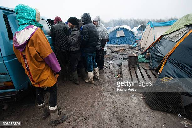 Refugees in the refugee camp in Dunkirk wait in line for food donations at the refugee camp in Dunkirk where rain and winter conditions make life...