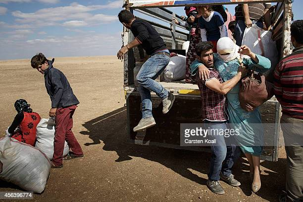 Refugees jump from a truck after crossing the border from Syria into Turkey September 30 2014 near Suruc Turkey Kurdish troops are engaged in a...