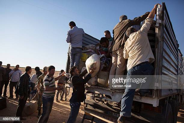 Refugees lift belongings into the back of a truck after crossing the border from Syria into Turkey on October 1 2014 near Suruc Turkey Kurdish troops...