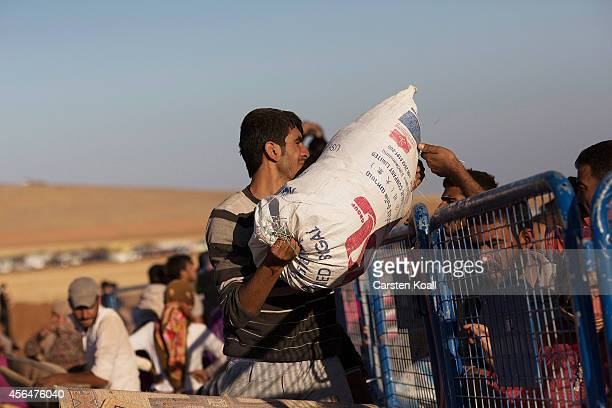 Refugees lift their belongings over the fence as they cross the border from Syria into Turkey on October 1 2014 near Suruc Turkey Kurdish troops are...