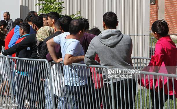 Refugees line up at a temporary shelter for asylum seekers in Giessen western Germany on September 10 2015 Around 450000 refugees have arrived in...