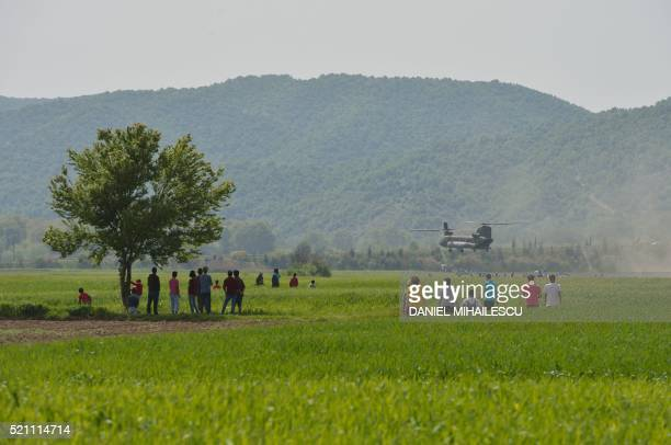TOPSHOT Refugees look at a military drill at the makeshift camp at the GreekMacedonian border near the village of Idomeni on April 14 2016 According...