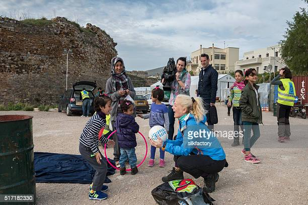 Refugees, NGO volunteers and TV team at Greek refugee camp