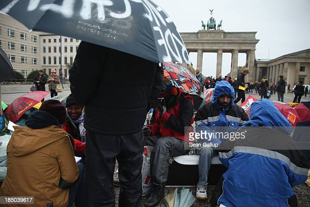 Refugees on the 8th day of a hunger strike lie and sit in front of the Brandenburg Gate on October 17 2013 in Berlin Germany 28 refugees some of whom...