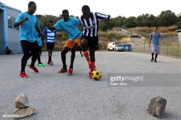 Refugees play soccer on a makeshift soccer field on a private locked parking lot outside the Moria refugee camp on May 20 2018 in Mytilene Greece...