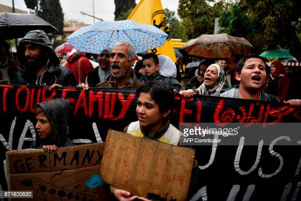 Refugees protest outside the German embassy in Athens under pouring rain on November 8 to demand a faster family reunification process in Germany...