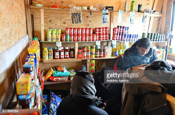 """Refugees provide goods from refugee-run store at the camp known as the """"Wild Jungle"""" on February 23, 2015 in Calais, France as evacuation deadline..."""