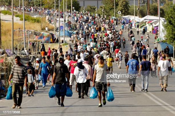 Refugees queue for food and water in the northeast of the capitol on the Greek island of Lesbos on September 13, 2020 in Mytilene, Greece. A massive...