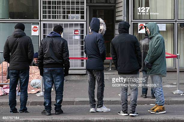Refugees queue up in front of the refugee reception platform of France Terre d'asile NGO on boulevard de la Villette northern Paris on January 26...