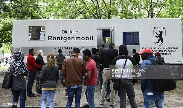 Refugees queue up next to a mobile medical xray centre at the 'State Office of Health and Social Affairs' in Berlin's Moabit district on July 31 2015...