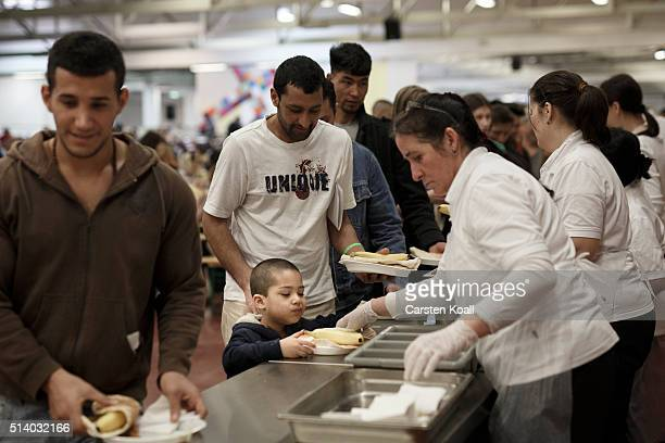 Refugees receive food during the 139th anniversary celebration of the Berlin Stadtmission at a shelter for refugees run by the charity on March 6...