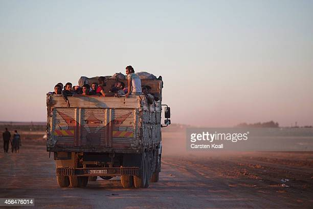 Refugees ride in the back of a truck after crossing the border from Syria into Turkey on October 1 2014 near Suruc Turkey Kurdish troops are engaged...