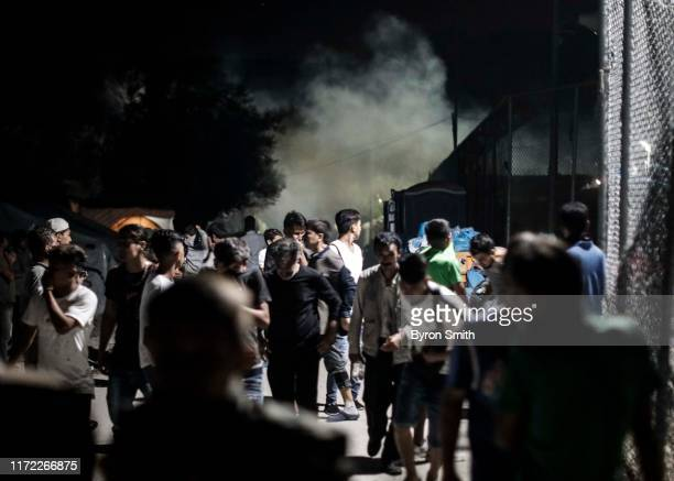Refugees run from teargas fired by Greek police hours after a fire inside of Moria refugee camp on the island of Lesbos on September 29 2019 in...
