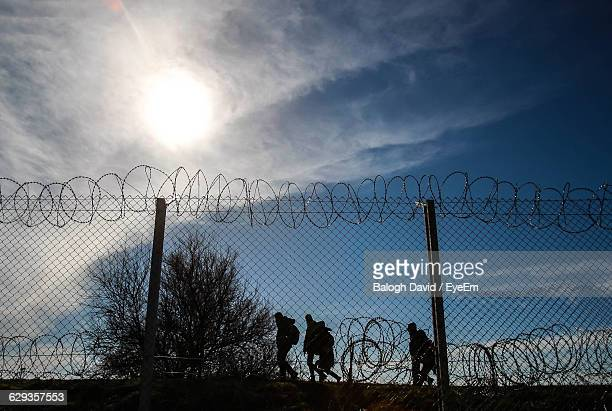 refugees running on border against sky - emigration and immigration stock pictures, royalty-free photos & images