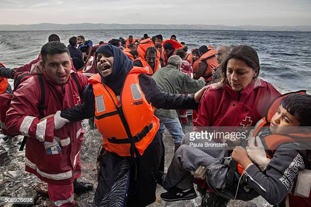 Refugees scramble over the rocks after another over crowded raft lands from Turkey on October 27 in Lesbos Greece Winter seas have done little to...