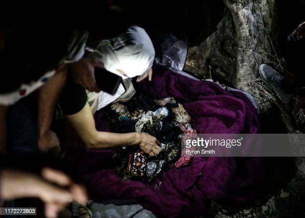 Refugees show off what may be the charred remains of an infant who was allegedly killed in a blaze at Moria refugee camp on the island of Lesbos on...