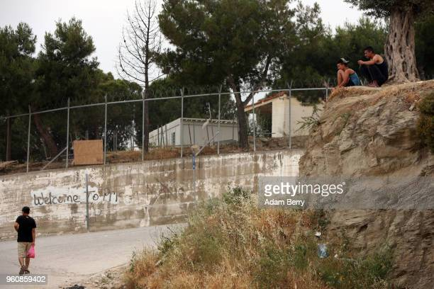Refugees sit above graffiti reading 'Welcome to Prison' at the entrance to the Moria refugee camp on May 20 2018 in Mytilene Greece Despite being...