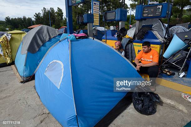 Refugees sit near their tents located just next to the gas pumps at the gas station of Hotel Hara a roadside bungalow in the village of Evzoni seven...