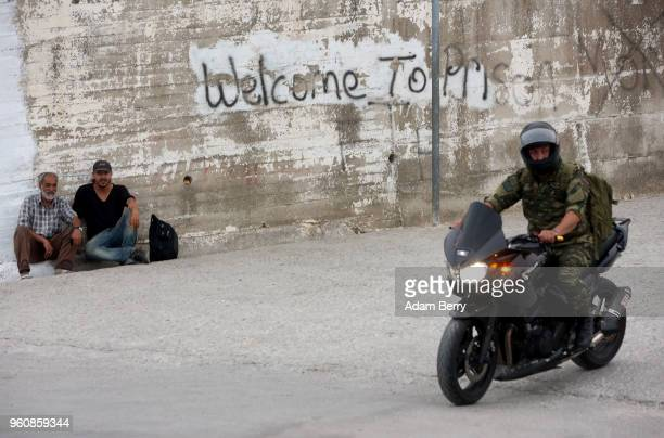 Refugees sit next to graffiti reading 'Welcome to Prison' as a military officer passes on a motorcycle at the entrance to the Moria refugee camp on...