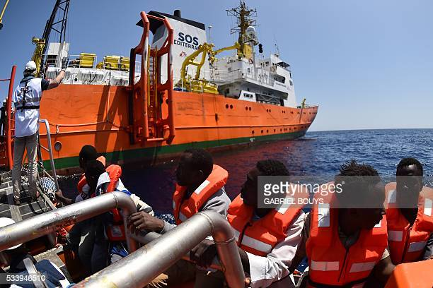 Refugees sit on a boat during a rescue operation of migrants and refugees at sea of the 'Aquarius' a former North Atlantic fisheries protection ship...