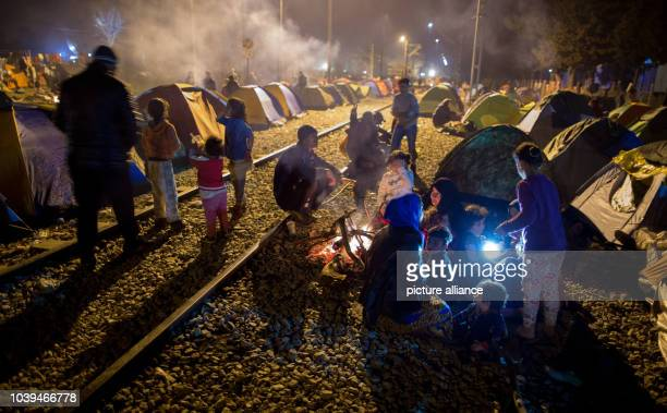 Refugees sit on train tracks by a campfire in front of their tents in the refugee camp at the Greek-Macedonian border in Idomeni, Greece, 05 March...
