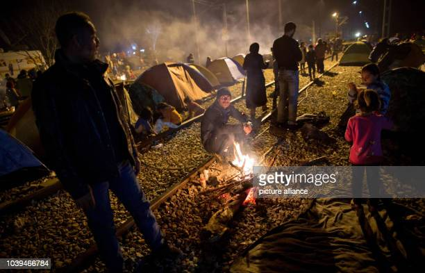 Refugees sit on train tracks by a campfire in front of their tents in the refugee camp at the GreekMacedonian border in Idomeni Greece 05 March 2015...