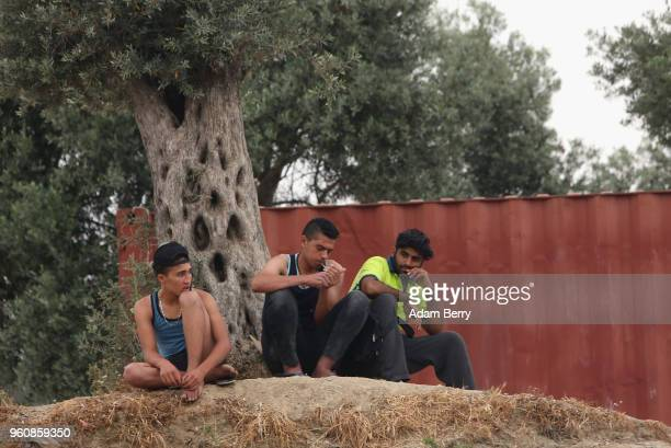 Refugees sit outside the Moria refugee camp on May 20 2018 in Mytilene Greece Despite being built to hold only 2500 people the camp on the Greek...