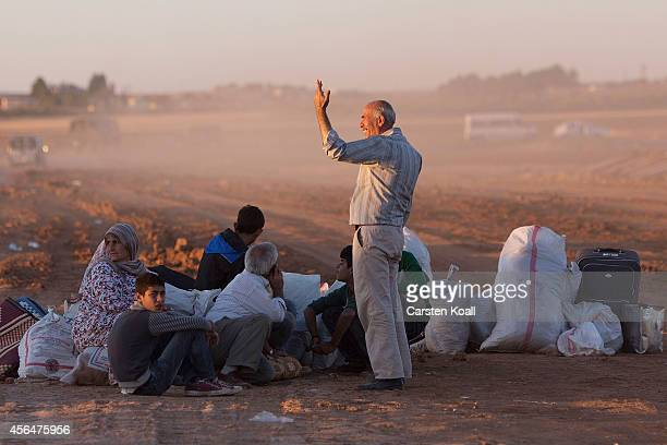 Refugees sit with their belongings after crossing the border from Syria into Turkey on October 1 2014 near Suruc Turkey Kurdish troops are engaged in...
