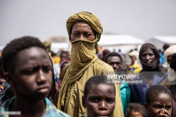 Refugees stand in Goudebou, a camp that welcomes more than 11,000 Malian refugees in northern Burkina Faso, on International Refugee Day on June 20,...