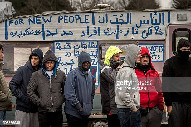 TOPSHOT Refugees stand in the socalled 'Jungle' migrant camp in Calais northern France on February 6 2016 / AFP / PHILIPPE HUGUEN