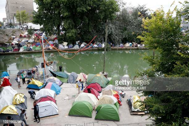 Refugees stand next to tents in a makeshift camp along the St-Denis canal in Aubervilliers near Paris on July 17, 2020.