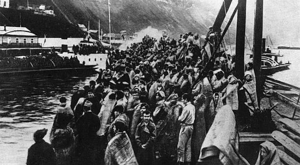 Refugees stand on the deck of a ship during the Russian...