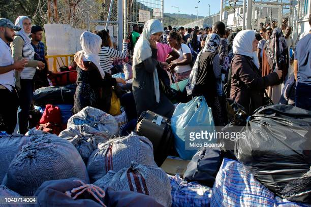 Refugees stand with their belongings as they wait to board a bus which will take them to port of Mytilene where they plan to board a ferry to Athens...