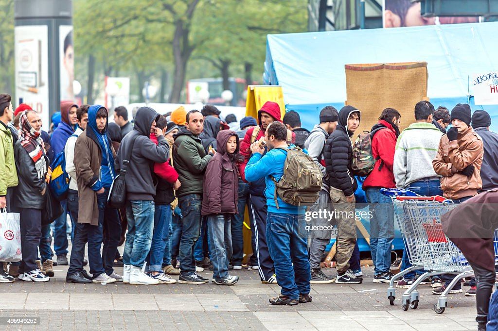 Refugees standing in a row : Stock Photo