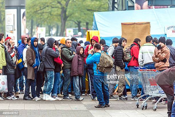 refugees standing in a row - germany stock pictures, royalty-free photos & images
