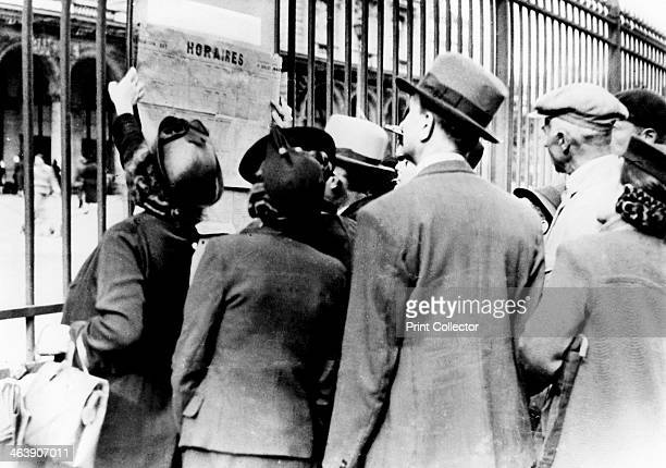 Refugees studying a train timetable Gare de l'Est Paris July 1940 People who had fled the German invaders preparing to return to their homes after...