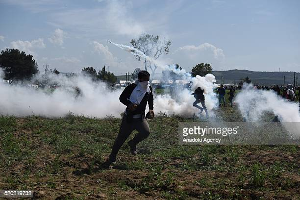 Refugees throw tear gas capsules back to Macedonian riot police at Greece-Macedonia border, in Idomeni, Greece on April 10, 2016.