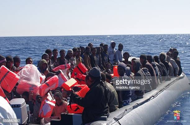 Refugees trying to pass Europe are seen on a boat at the middle of the Mediterranean Sea before Italian security forces rescued them at the...
