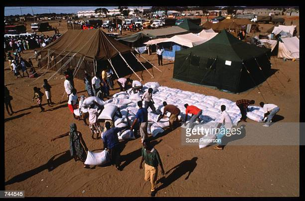 Refugees unload food from a United Nations convoy March 24 1993 in Caimbambo Angola Despite a 1991 peace treaty the West African nation is again...