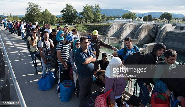 Refugees wait at the GermanAustrian border where they were stopped by the police on September 16 2015 in Freilassing Germany