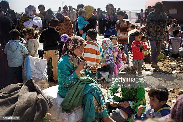 Refugees wait behind a fence before they cross the border from Syria into Turkey September 30 2014 near Suruc Turkey Kurdish troops are engaged in a...