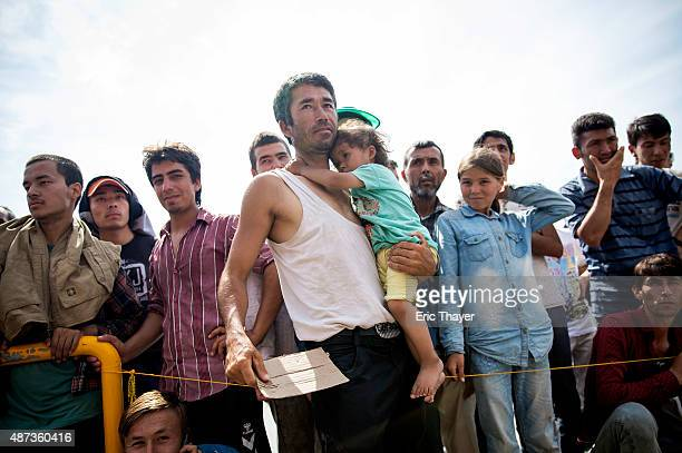 Refugees wait in line for ferry tickets at the port in Mytilini on September 9 2015 in Lesbos Greece Greece has been overwhelmed this year by record...
