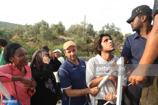 Refugees wait in line for food at an independent NGOrun food distribution center outside the Moria refugee camp on May 20 2018 in Mytilene Greece...