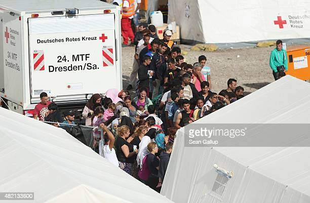 Refugees wait in line inside a temporary tent camp on July 27 2015 in Dresden GermanyThe German Red Cross set up the camp last week and plan to house...