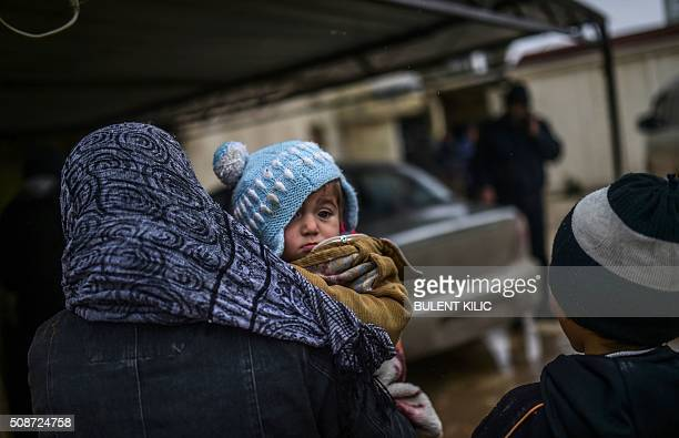 Refugees wait near the Turkish border crossing gate as Syrians fleeing the northern embattled city of Aleppo wait on February 6 2016 in Bab alSalama...