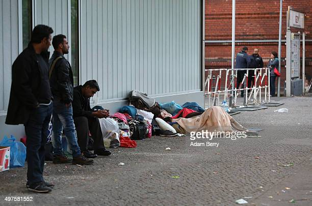 Refugees wait outside the LaGeSo State Office for Health and Social Services the office for registering migrants on September 26 2015 in Berlin...